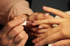 A student at the training courses of manicure applies color gel shell. color pink gold.  Royalty Free Stock Photo