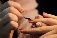 A student at the training courses of manicure prepares the hand of the client before applying shellac. application on. The nails of the protective finish Stock Image