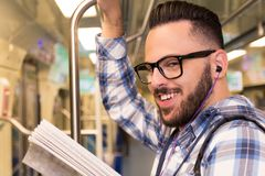 Student traveler with glasses reading book while riding to school by subway train. Concept of commute, effort, aspirations. Student traveler young man with royalty free stock photography