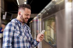Student traveler waiting for train listening to music on a smartphone. Concept of leisure, communication, social media. Student traveler young man waiting for stock image