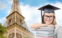 Student in trencher with books over eiffel tower Stock Photos