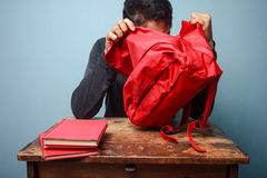 Student trying to find something in his bag. Student is at an old desk trying to find something in his bag Royalty Free Stock Photo