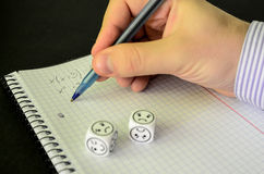 Student trying to solve mathematical equation without success. On black background, sad dices - stock photo stock images