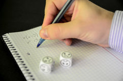 Student trying to solve mathematical equation without success. On black background, sad dices - stock photo royalty free stock photo