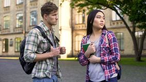 Student trying to talk with his asian girlfriend near college, quarrel, break-up stock image