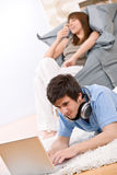 Student - Two teenager with laptop and headphones. Woman eat ice cream sitting on bean bag Stock Images