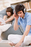 Student - Two teenager with laptop and headphones. Woman reading book relaxing Stock Image