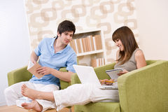 Student - two teenager reading book home. Student - two teenager reading book in lounge, sitting on armchair Stock Photos