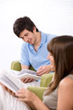 Student - two teenager reading book home. Student - two teenager reading book in lounge, sitting on armchair Royalty Free Stock Photos