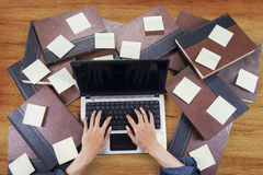 Student typing with laptop around books 1 Stock Image