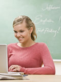 Student typing on laptop in classroom Royalty Free Stock Photos