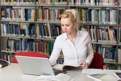 Student Typing on Laptop in the University Library. In the Library - Pretty Female Student With Books Working in a High School - University Library - Shallow royalty free stock photo