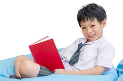 Student in uniform reading book over white. Asian boy student in uniform reading book over white Stock Image