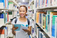 Student in university library. Cheerful female african american student in university library stock photos