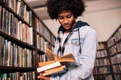 Student uniwersytetu pozycja w bibliotece z udziałami książki Fotografia Stock