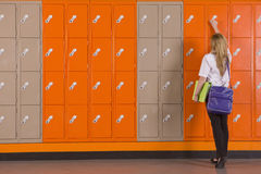 Student unlocking school locker Stock Image