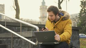 Student uses laptop and talks on phone in park. Student sits on the bench in park. Young guy uses laptop and talks on the phone preparing to exams alone stock footage