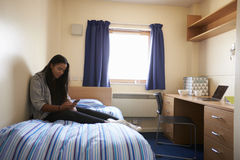 Student Uses Mobile Phone In Bedroom Of Campus Accommodation royalty free stock photo