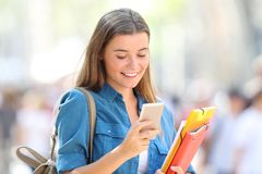 Student uses a smart phone in the street. Happy student uses a smart phone walking in the street Royalty Free Stock Photography