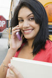 Student Using Cell Phone By School Bus Stock Photo