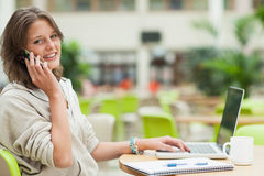 Student using cellphone and laptop at cafeteria table Stock Photo