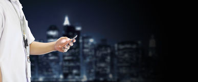 Student Using Cellphone in Skyline Background. School Student boy is using a cellphone in a blurred skyline background. Wide size photo. Subject is on the side Stock Photos