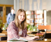 Student using computer in a library. looking at camera Stock Photos