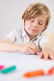 Student using crayons to draw Stock Photography