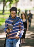 Student Using Digital Tablet On Campus. Young male student using digital tablet on campus with friends in background Stock Image