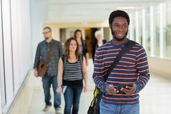 Student Using Digital Tablet Down University. Young male university student with digital tablet standing on university corridor Stock Photos