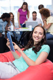 Student using digital tablet with friends in background. Smiling female student using digital tablet with friends in background Stock Photos