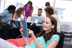 Student using digital tablet with friends in background. Smiling female student using digital tablet with friends in background Royalty Free Stock Images