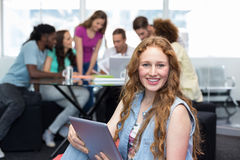 Student using digital tablet with friends in background. Smiling female student using digital tablet with friends in background Royalty Free Stock Photos