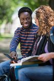 Student Using Digital Tablet With Friends On. Happy male university student using digital tablet with female friends on campus Stock Photos