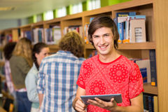 Student using digital tablet in library. Male college student using digital tablet in the library Royalty Free Stock Photography