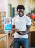 Student Using Digital Tablet In Library. Young male student using digital tablet in library Stock Photography