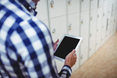 Student using digital tablet in locker room. At college Royalty Free Stock Image
