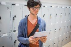 Student using digital tablet in locker room Royalty Free Stock Photos