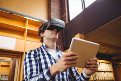 Student using digital tablet and virtual reality headset in library. Student using digital tablet and virtual headset in library at college Stock Images