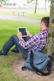 Student using his tablet pc outside leaning on tree Royalty Free Stock Photo