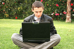 Student using laptop. On green grass Stock Image