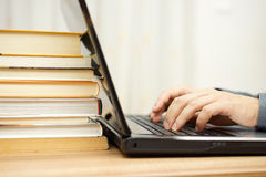 Student is using laptop and books to prepare for exam Stock Photo