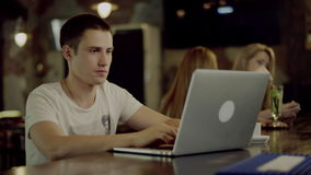 Student using laptop in a cafe. Male serious student using laptop in a cafe, two women on background stock footage