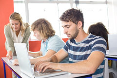 Student using laptop in classroom. Male student using laptop in the classroom Royalty Free Stock Photos