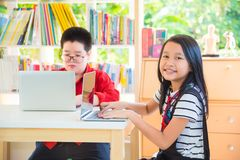 Student using laptop computer in library. Asian student using laptop computer in school library Royalty Free Stock Photo
