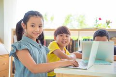 Student using laptop computer in school library. Young asian student using laptop computer in school library Royalty Free Stock Photos
