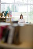Student Using Laptop In Library. Female university student using laptop in library Stock Photo