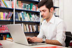 Student using a laptop in a library Stock Photo