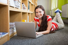 Student using laptop lying on library floor Royalty Free Stock Photography