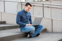 Student using laptop. University student smiling outdoors using his laptop with free wifi on Campus area sitting on stairs. A confident student holding his stock photography